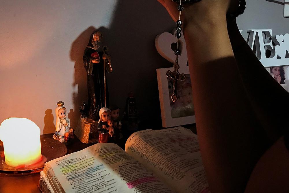 Karliany faz uma oração com terço na mão para santo ao lado de Bíblia e vela