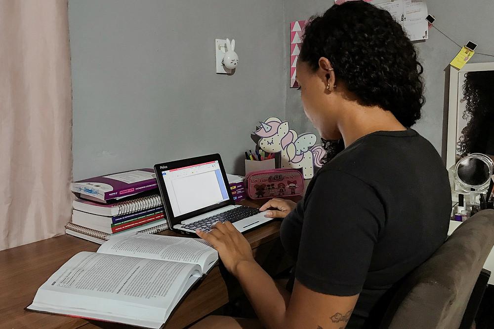 Karliany está sentada numa cadeira de frente para uma mesa de estudos, com livros abertos e notebook ligado