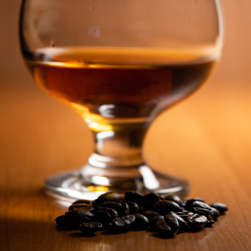 Cognac glass with brandy, coffee beans n