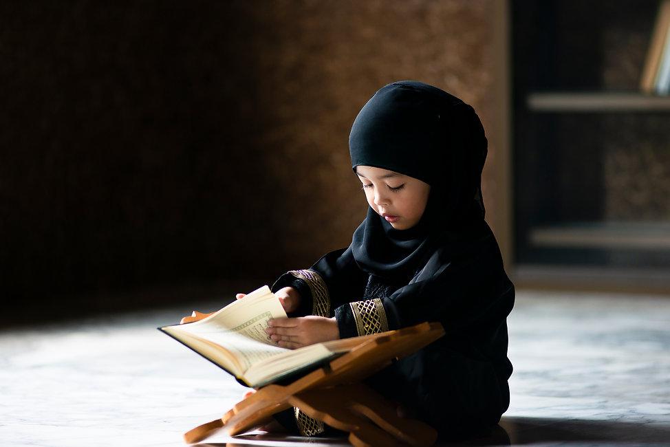 Asian Indonesian Muslim kid is reading t