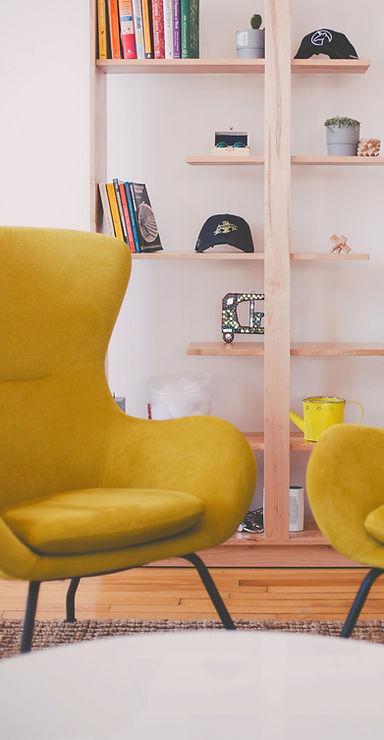 zwei gelbe Sessel in gemütlich wirkendem Raum mit heller Birke gestaltet
