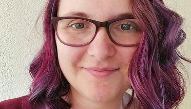 Website Host, weiblich, violette Haare, Brillenträgerin, lächelnd