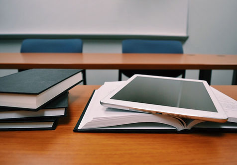 Books and ipad on a desk in classroom