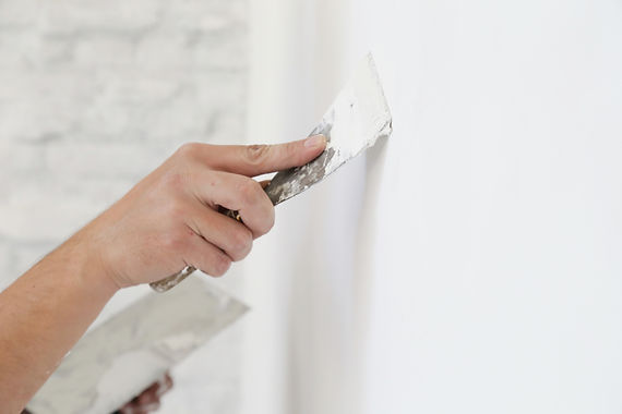 Plastering wall with putty-knife, close