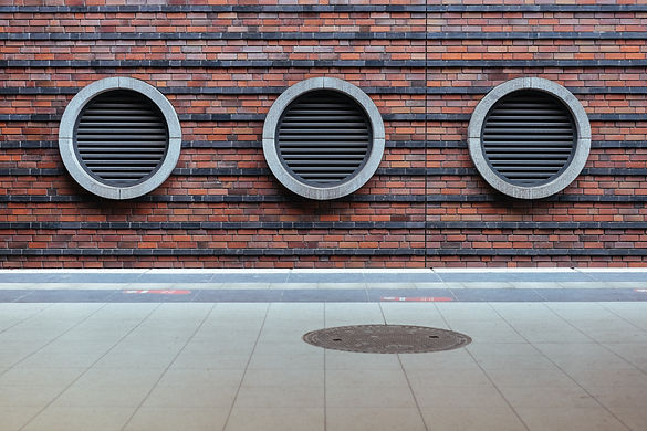 Three circular grills along a brick wall echo the round manhole cover on the ground.