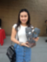 Jessica Pham receiving a sculpture as a prize in the Red Shuttleworth poetry contest.