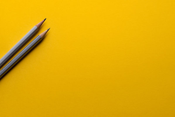 The image shows two gray pencils stretched out on a mustard-yellow backdrop.