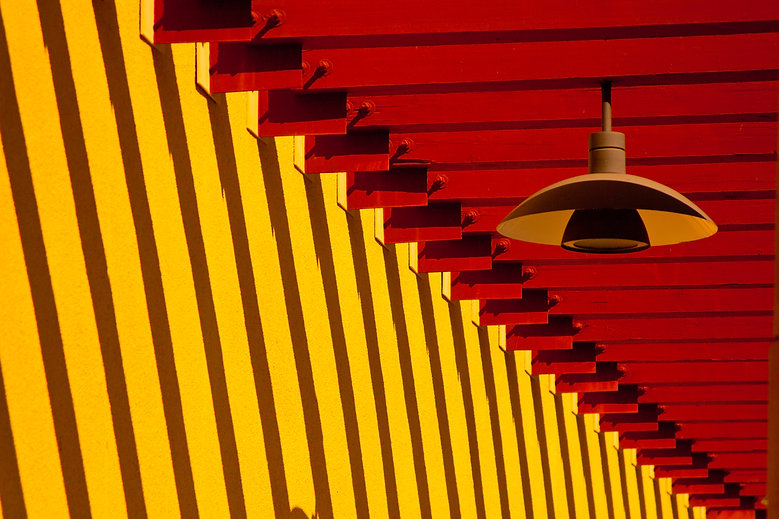 An orange lamp dangles in front of bright yellow and red intersecting walls.