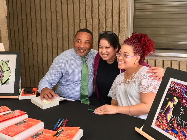 Alfred Carter Jr. and Victoria Baptiste, desendants of Henrietta Lacks, pose with student Janiel Victorino at a book signing.