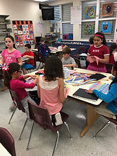 Students working on weaving projects with colored paper in art class