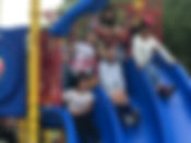 Students at the top of the triple slide in the playground