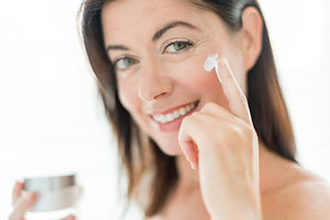 portrait of a beautiful mature lady preventing wrinkles by using a luxurious face lotion.j