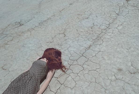 Girl Lying on Dry Ground