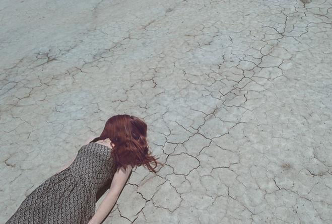 Fille couchée sur un sol sec