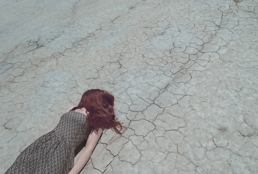 Girl Lying on Dry Ground