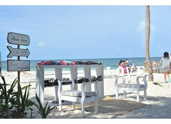 A sitting area on the beach with shoe valet for wedding ceremony