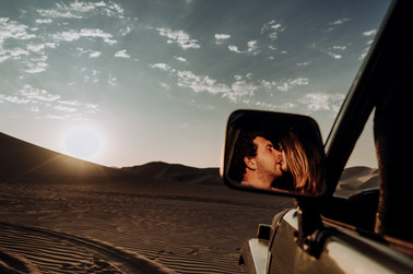 Man and woman kissing reflection on a mirror of a 4x4 on the desert