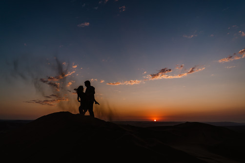 Man and woman standing on a dune at sunset