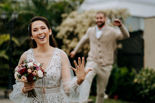 Happy bride showing her ring finger, groom jumping with joy at the back