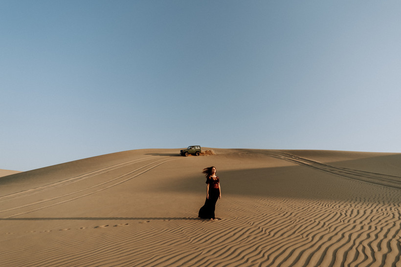 A woman standing in the middle of a dune. On the back, a 4x4 passing by