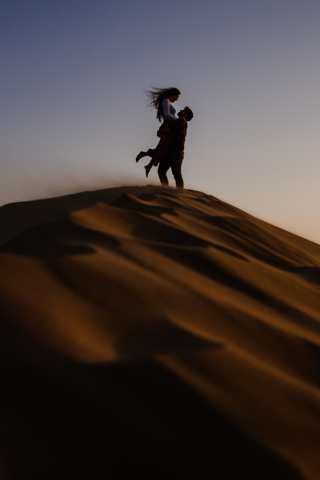 Man carrying woman on top of a dune