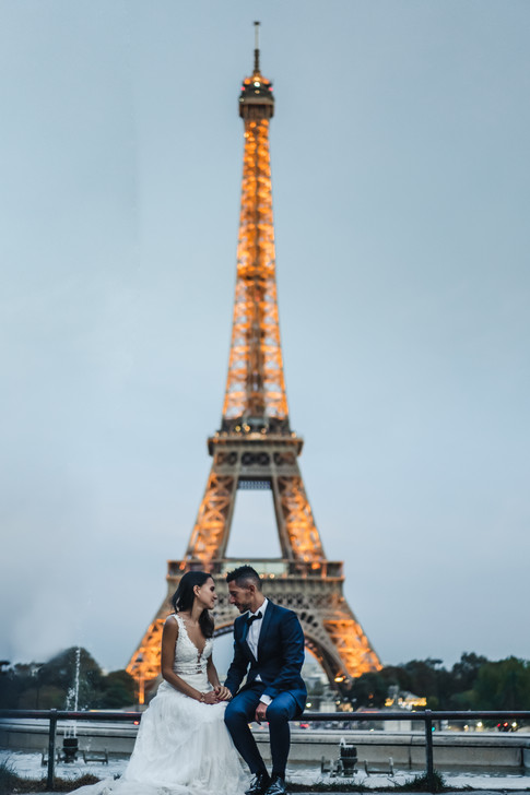 Bride and groom siting in front of the Eiffel Tower