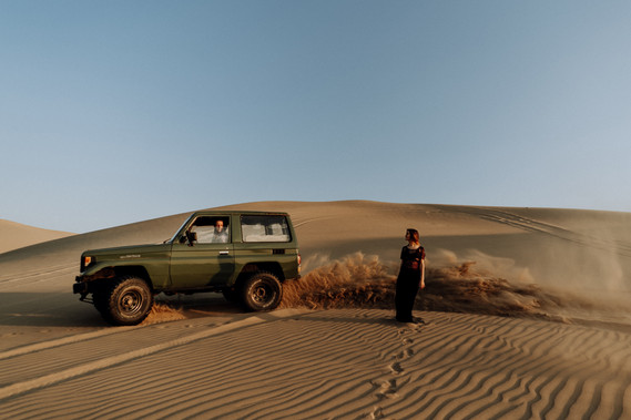 A man passes behind a woman on his 4x4 creating a sand cloud on a dune