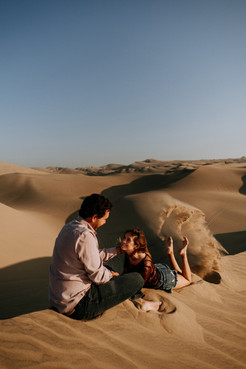Man siting on a dune, woman in front of him lifting sand with her feet