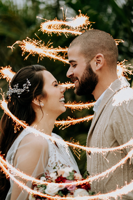 Bride and groom smiling at each other. A sparkling light twirls around them