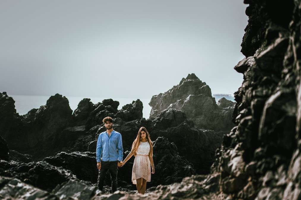 Man and woman holding hands standing on rocks