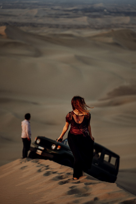 Woman walking, her hair flying over her face. Behind her a man next to a 4x4. The setting is the desert