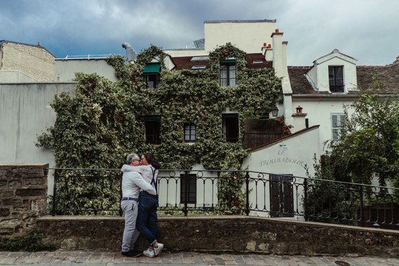 A man and woman hugging in front of a house at Montmartre, France