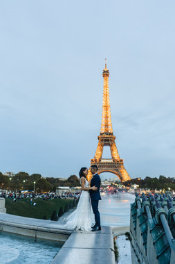 Bride and groom standing in front of the Eiffel Tower