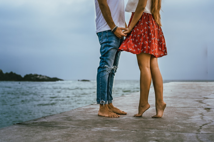 The bottoms of a girl and boy holding hands at a pier