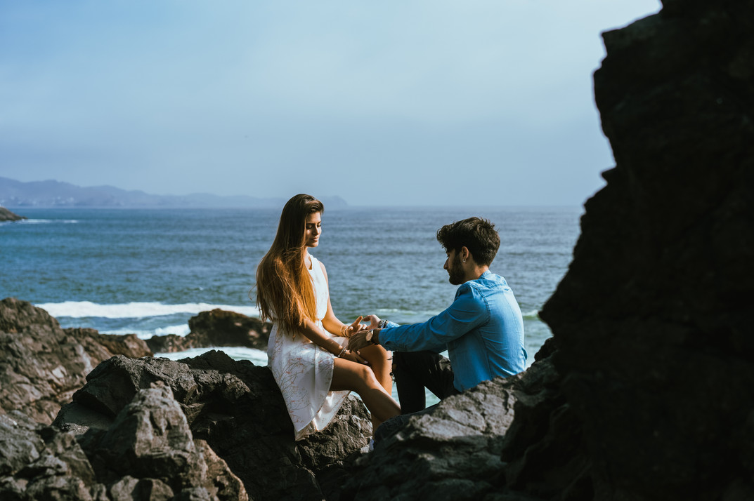 Man and woman holding hands siting on some rocks next to the ocean