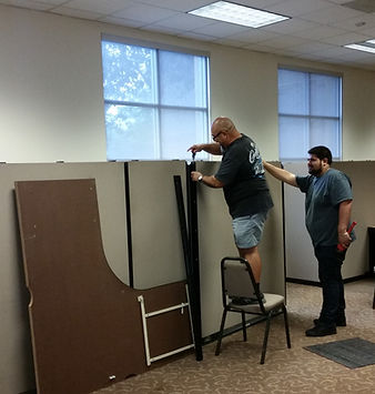 Volunteer helping board member setup office cubicles