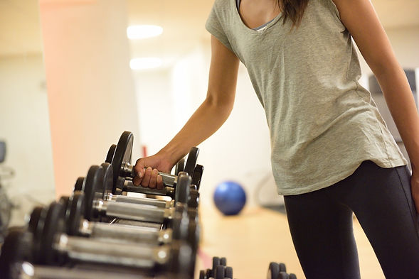 Gym woman strength training lifting dumb
