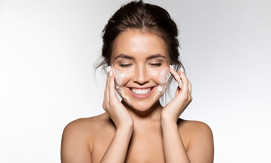 Portrait of cheerful laughing woman applying foam for washing on her face. Lovely brunette