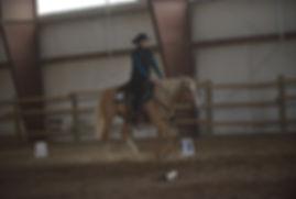 A woman schools her horse on a Cowboy Dressage court.