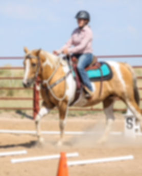 A woman rides her palomino paint in a Cowboy Dressage test