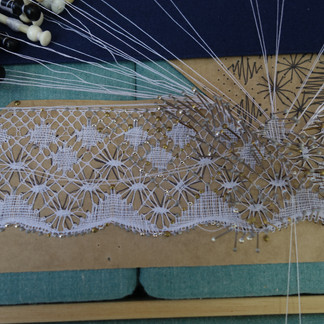 Turning the corner on a wide Torchon lace edging.