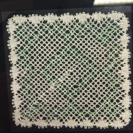 A completed torchon mat in a coaster mount