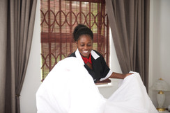 Happy housemaid change bed sheets in roo