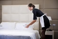 Maid making bed in hotel room.jpg