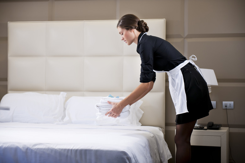 Maid making bed in hotel room.jpg