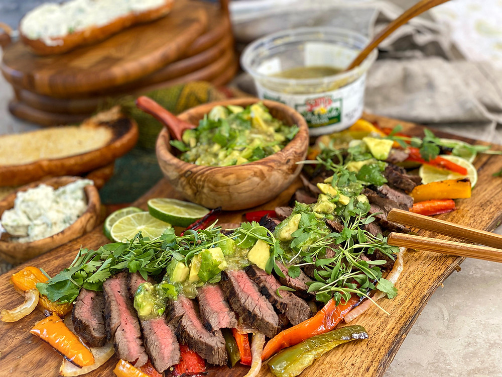 A platter of steak, topped with avocado salsa verde.