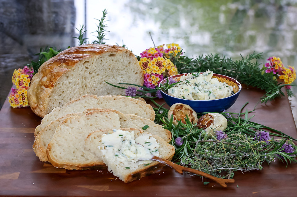 Sliced sourdough bread with roasted garlic herb butter.