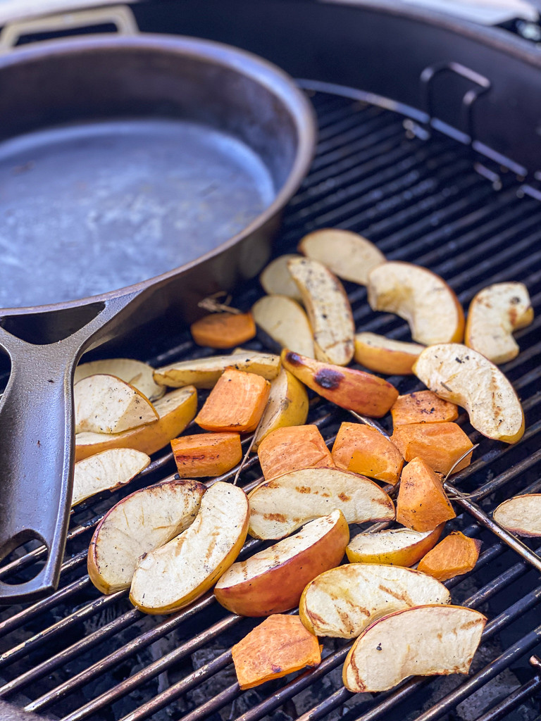 Skillet on grill with apples and persimmons roasting.