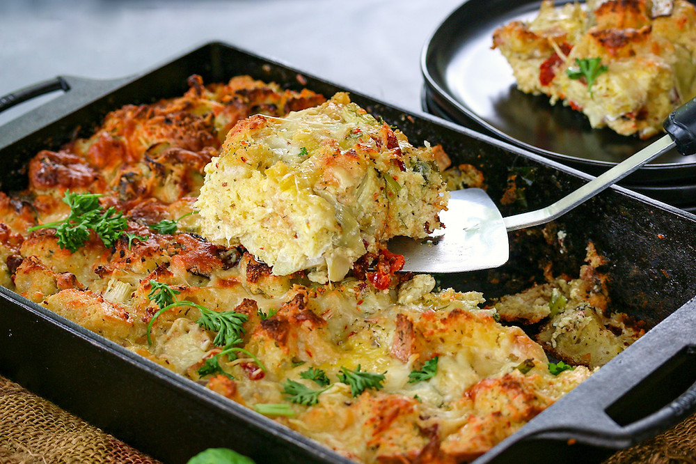 A cheesy bread pudding strata that is filled with artichokes, bacon, and sun-dried tomatoes.