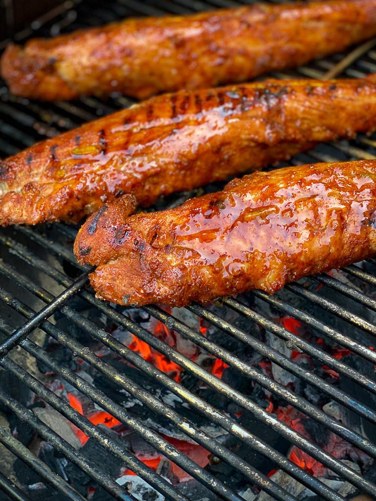 Three glazed pork tenderloins on the grill.